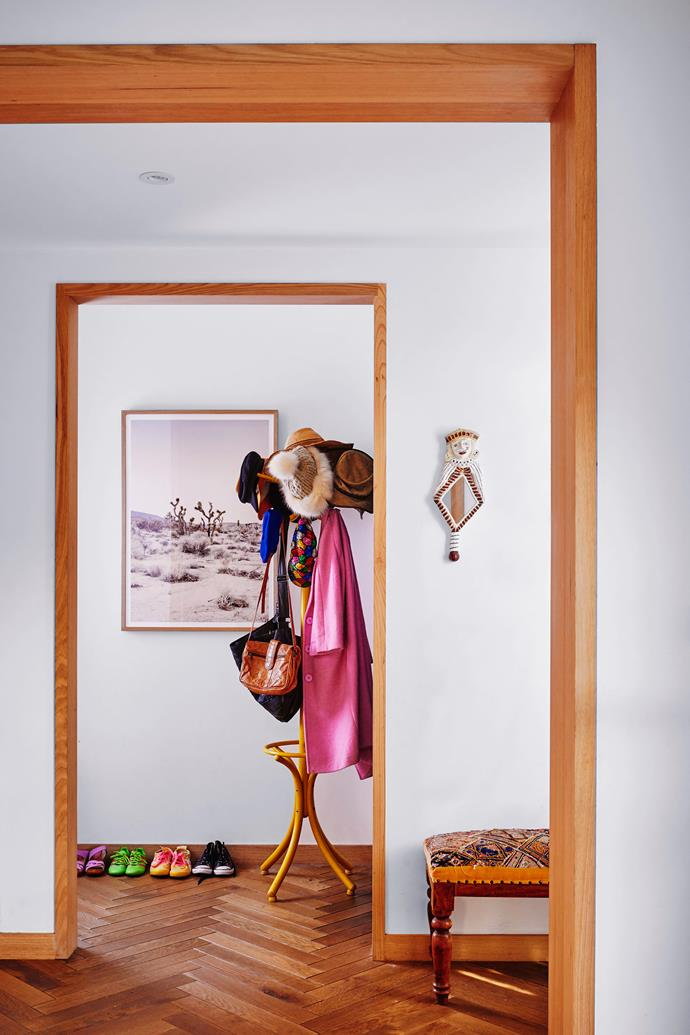 The home's entryway is a sign of things to come: splashes of colour and beautiful American oak parquetry that flows throughout. A photo from The Artwork Stylist hangs next to a vintage yellow coat stand.