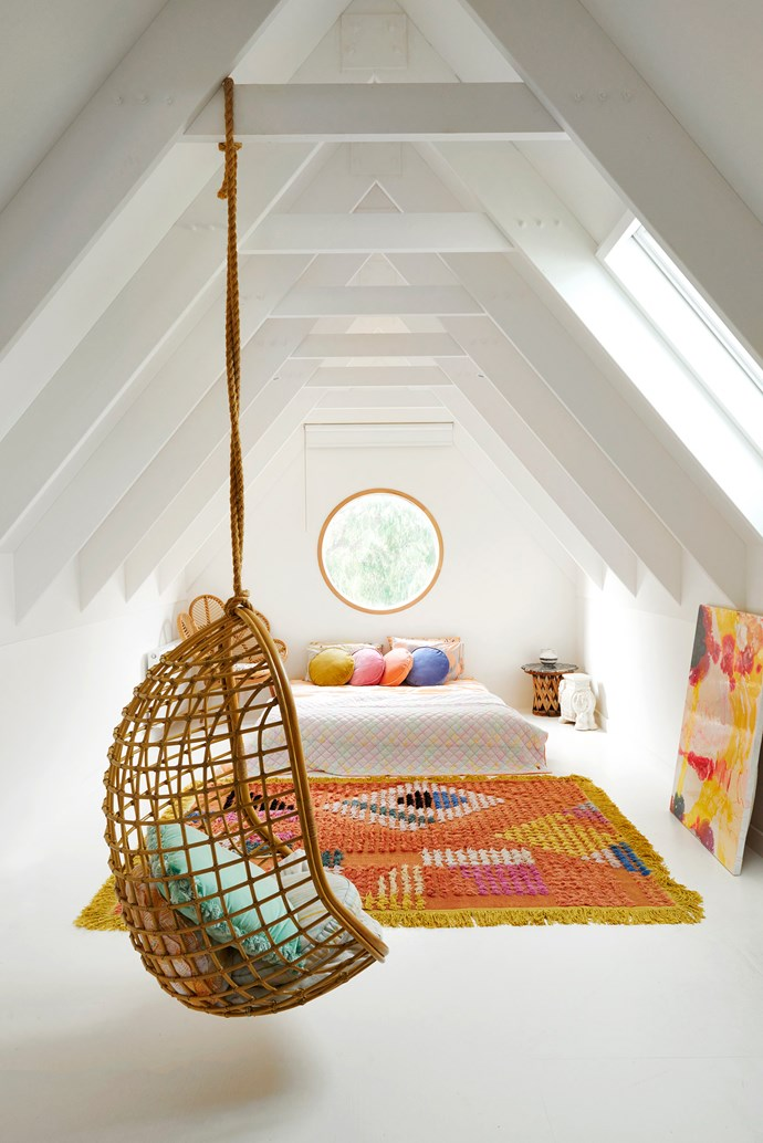 "The loft is used as a spare room for family and friends, who can relax in the swing chair from Byron Bay Hanging Chairs. The couple put in some round windows throughout. ""I have always had an affinity for round windows and curved walls,"" Hayley says. ""They add a real softness and ambience to a space."""