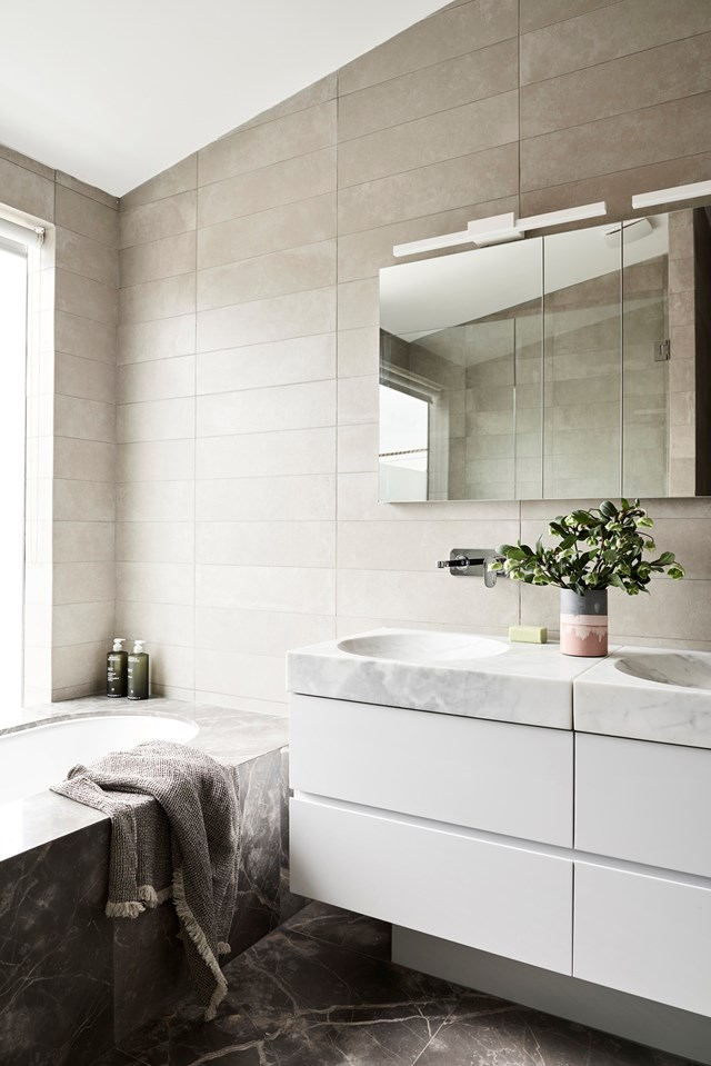 "Minimalist Japanese design inspired the look and feel of this bathroom in a [Melbourne famiy home](https://www.homestolove.com.au/melbourne-japanese-industrial-home-6051|target=""_blank""). The inset tub, clad in Fior Di Bosco marble is a delight to the senses. *Photo: Eve Wilson / Styling: Ruth Welsby / Story: Australian House & Garden*"