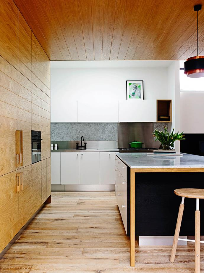 **TOTALLY WRAPPED** <br><br> Interior designer Amber Ma of [Austin Design Associates] clad the bulkhead of this kitchen in American oak and used the same timber for a wall of joinery that conceals the walk-in pantry, and the integrated Liebherr fridge/freezer with timber handles. *Photo: Australian House & Garden*