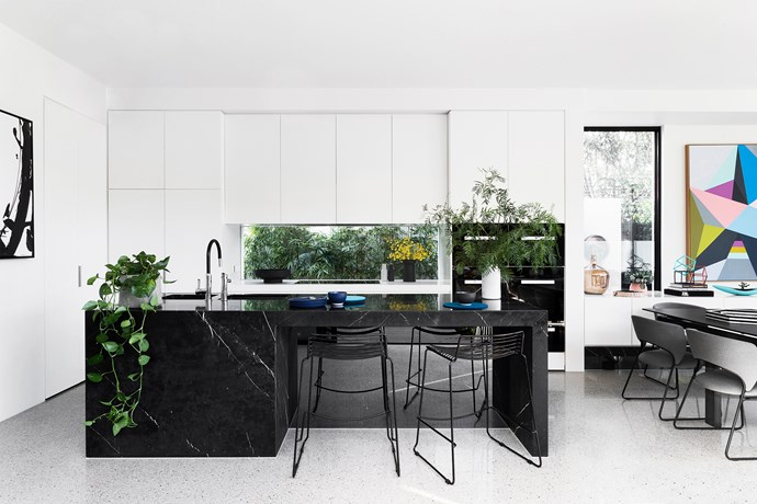 White semi-gloss cabinetry rises to the ceiling while black in the appliances, furniture and island bench's stunning Nero Maquina marble rules at ground level.