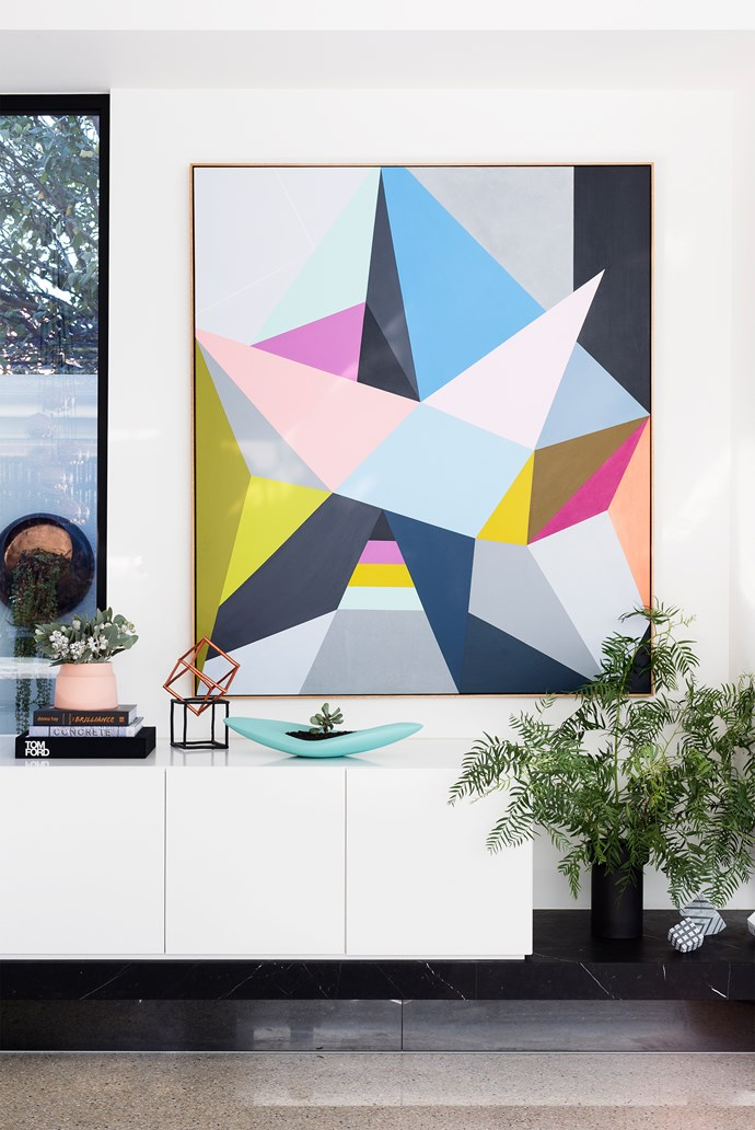 The large triangles in the artwork by Louise de Weger were the starting point for the room's colour scheme. Blue plant pot from Rachael Swift Design.