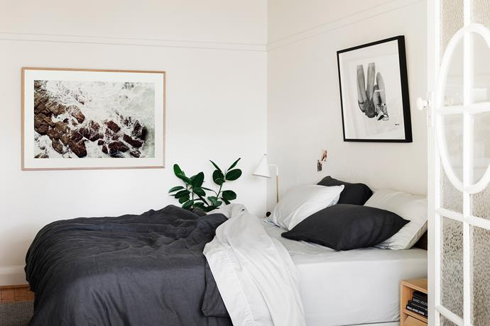 """""""We prefer calm tones for the bedroom. If we want to add colour I change the quilt cover,"""" Lucy says. The artwork above the bed is by graffiti street artist Doctor and features the words """"young love never ages"""". The linen quilt cover set, table lamp and art print are all from Hunting For George."""