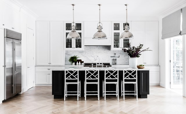 "Jonathan Adler 'Chippendale' counter stools from Coco Republic and 'Country Industrial' large pendants in polished nickel from Circa Lighting add a luxe touch to this classic Hamptons kitchen. [See the rest of this luxurious Hamptons style home](https://www.homestolove.com.au/a-luxurious-hamptons-style-home-in-sydneys-eastern-suburbs-6074|target=""_blank""). Photo: Maree Homer / *Belle*"