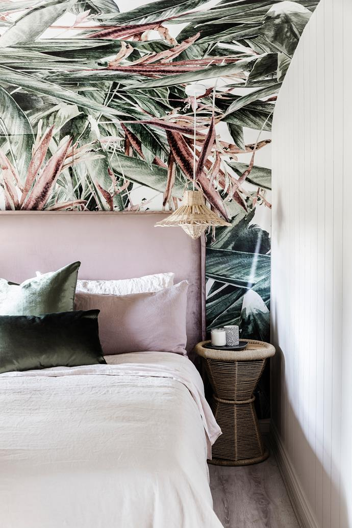 In an eye-catching move, the walls and curved ceiling of the master bedroom were covered with Watercolour Strelitzia wallpaper from Luxe Walls. A hanging rattan pendant from Newrybar Merchants casts a glow over the Cultiver bedlinen and bedhead from Heatherly Design.