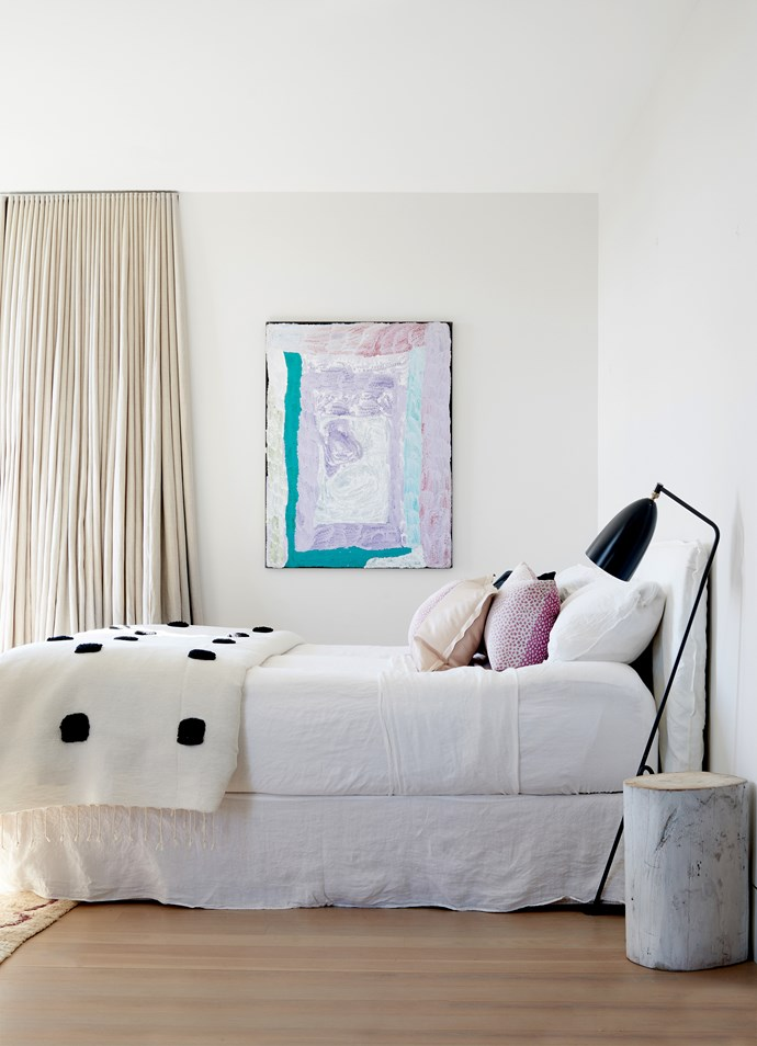 White linen bedhead from MCM House. Bed linen from Hale Mercantile Co. Gubi 'Grasshopper' floor lamp. Artwork by Lydia Balbal.