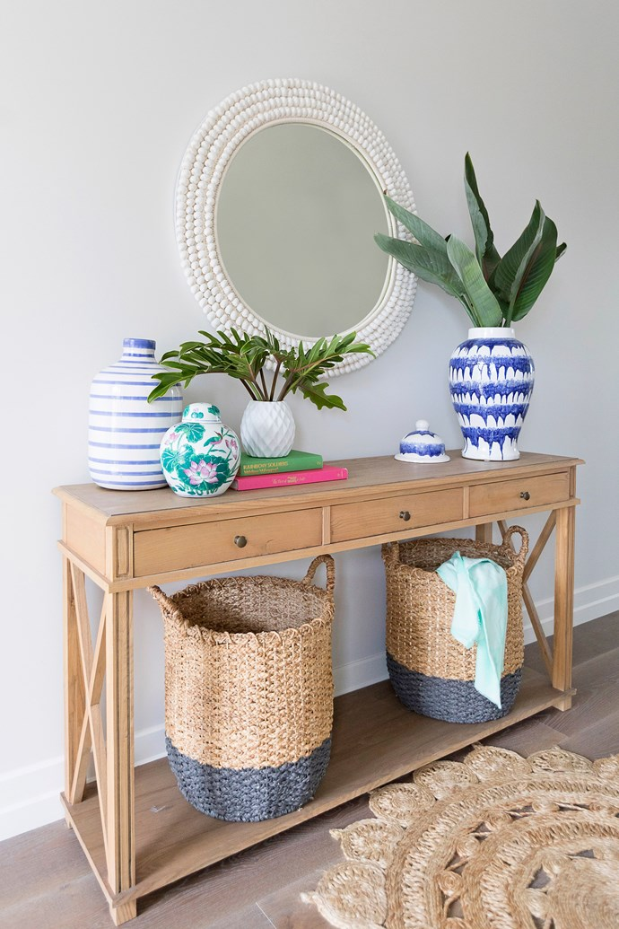 A timber hallway table styled with woven baskets, ginger jars and fresh greenery creates a warm welcome.