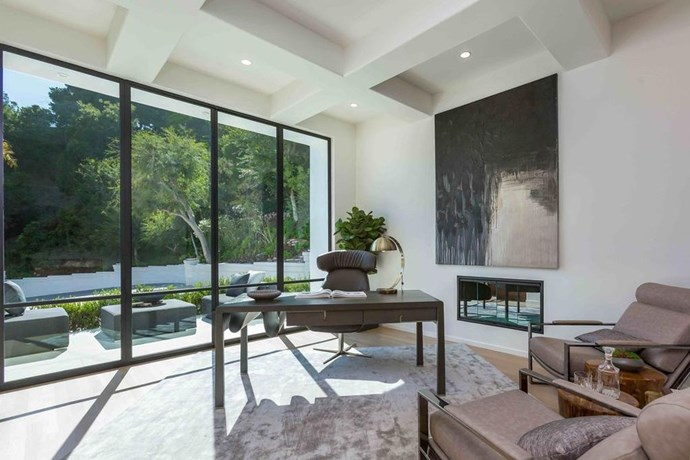 A study room with a view. The office is bathed in natural light thanks to minimalist floor to ceiling windows overlooking their private garden. Mid century modern furniture stays on beat with the rest of the house, which shares a classic, timeless interior.