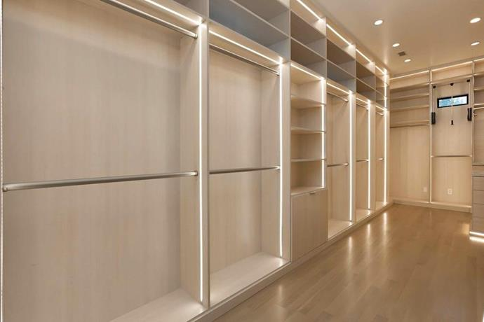 A walk-in-wardrobe with ample space and lots of functional lighting.