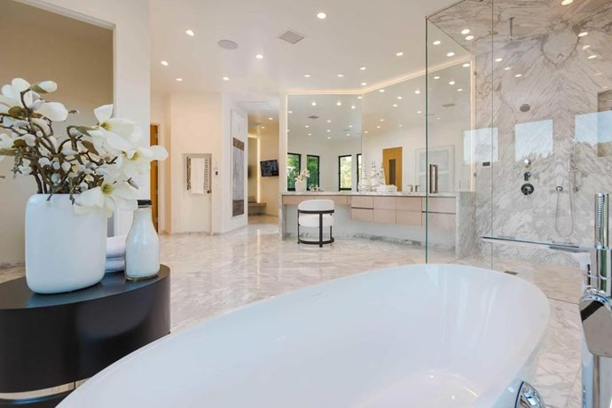 The spacious en-suite bathroom is fitted with a freestanding bath tub, a glass walk-in shower and large dressing table and vanity area. Obviously, generous lighting is a necessary part of any celebrity bathroom - hair and makeup artists alike will be thankful for this well-lit space.