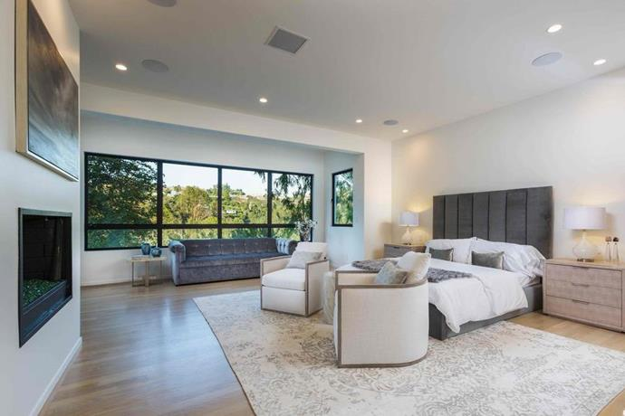 The master suite is fitted with all the bells and whistles, including a private den, bar, his and hers bathrooms, fireplace and a stunning walk-in-wardrobe. Wide-set windows feature views of Beverly Hills.