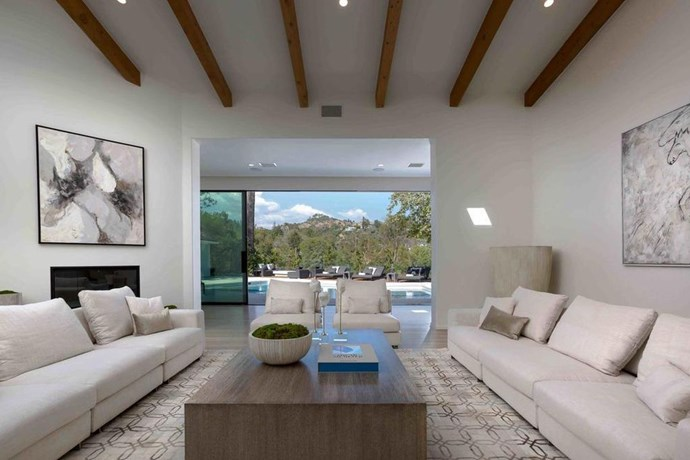 The informal family room comes equipped with a high, beamed ceiling and leads out into the outdoor seating area and swimming pool.