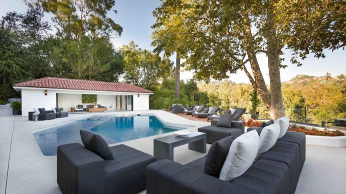 The outdoor seating area is already impressive with an al-fresco kitchen, swimming pool and views of the rolling Beverly Hills -  but is even more so when the sun sets.