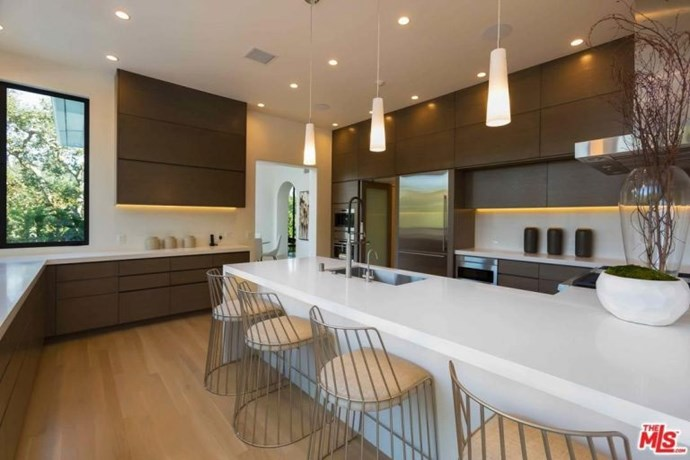 The chef's kitchen features a breakfast bar, designer stools and wooden flooring and cabinetry.