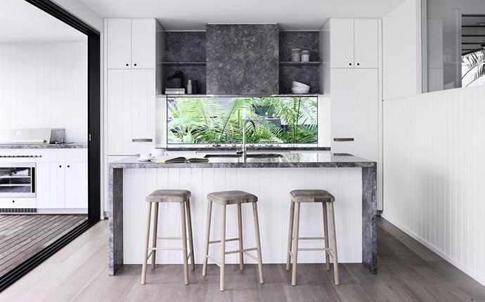 Cooks and guests enjoy the lush vignette of palms and ferns. Benchtops in Portsea Grey limestone from CDK Stone.