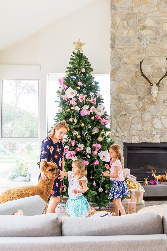 Loren, Isla and Chloe - with one of their two pet alpacas, Bambi - decorate the tree.