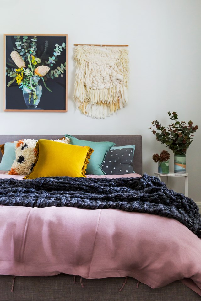 "There's no need to shy away from colour in Winter. Adding a luxurious woven throw to a bed and some fluffy cushions is a surefire way to make your bed look cosy. Draw some inspo from boho styling too, like this [bedroom in a Hamptons style home](https://www.homestolove.com.au/colourful-hamptons-style-home-6160|target=""_blank""), which features a unique handwoven macrame wall-hanging. *Photo: Katherine Jamison*"