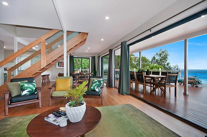 Breezy open plan living spaces open onto a sprawling deck with views over Wategoes Beach.