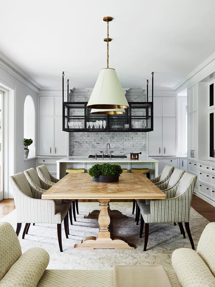 In the family meals area, custom-made table and chairs upholstered in Perennials 'Soho Stripe' from South Pacific Fabrics. Visual Comfort 'Goodman' pendants from Laura Kincade.