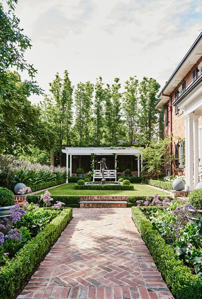 "This 1930s [Georgian Brick home](https://www.homestolove.com.au/1930s-georgian-brick-home-honours-late-designers-vision-5654|target=""_blank"")  is surrounded by manicured gardens that boast neatly trimmed hedges and clipped balls, which are framed by red brick inlays."