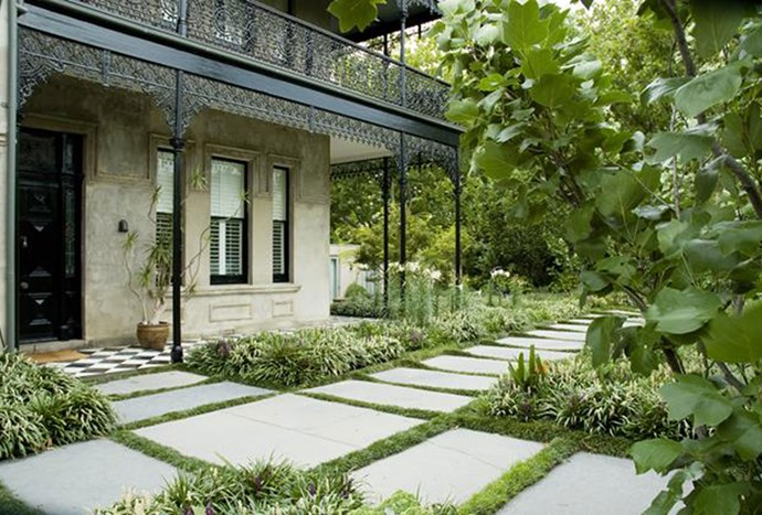 """Purple and white Liriope, mondo grass, huge slate flagstones and tall tulip trees complement the scale of the [surrounding home](https://www.homestolove.com.au/front-garden-design-ideas-that-add-value-to-your-home-5776