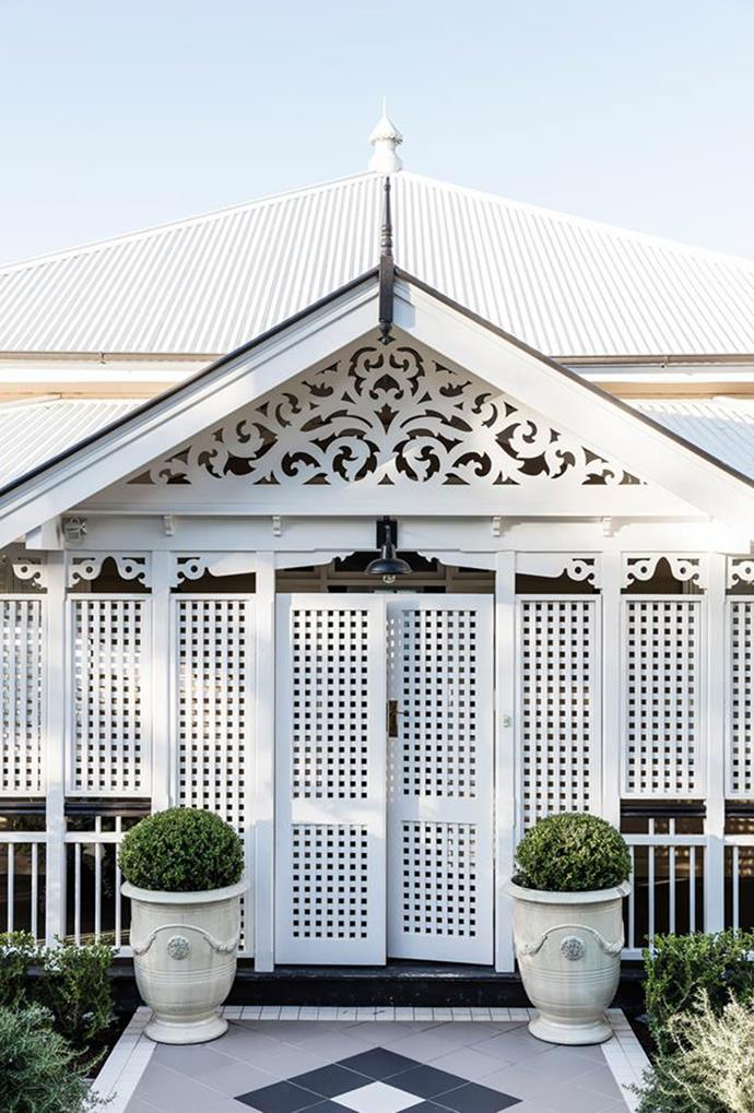 "Terracotta tiles, accented with [trimmed pot plants](https://www.homestolove.com.au/luxurious-renovation-of-an-old-timber-workers-cottage-5159|target=""_blank""), emphasise the detailed fretwork and latticework of the front entrance of this heritage-listed home. *Photography: Maree Homer*"
