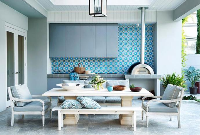 """The alfresco kitchen and dining area in this [Perth family home](https://www.homestolove.com.au/multi-functional-outdoor-living-room-designs-6029 target=""""_blank"""") puts practicality first. The kitchen is fully equipped with a barbecue grill, teppanyaki plate, integrated rangehood and under-bench fringe. The ceiling also incorporates louvres, ceiling fans and heaters for all-year round comfort."""