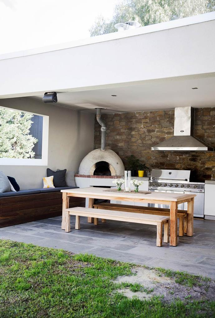 """A wooden table and bench seats, paired with built-in outdoor seating arrangements and a wood fired pizza oven are ideal for entertaining in this contemporary family [Californian bungalow](https://www.homestolove.com.au/californian-bungalow-opens-up-to-the-light-3674