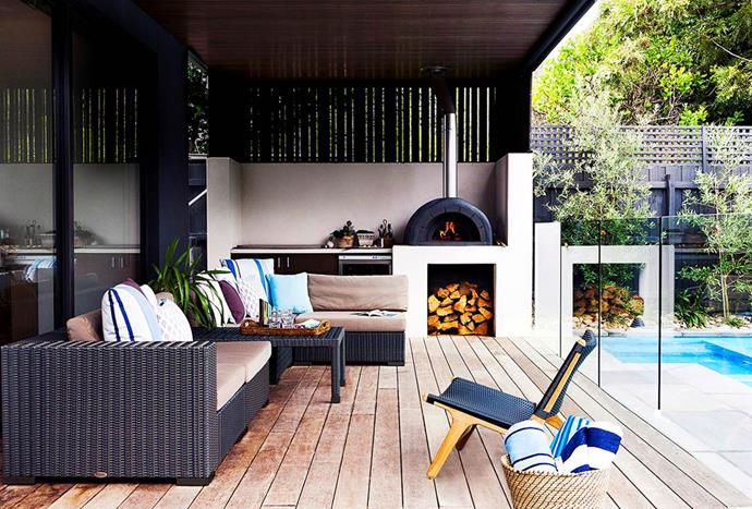 """Extra-wide merbau boards, ceiling cladding and wicker furniture pieces supplement the wood-fired oven and other kitchen essentials in this Melbourne [outdoor room](https://www.homestolove.com.au/6-outdoor-rooms-that-get-the-balance-right-1649 target=""""_blank"""")."""
