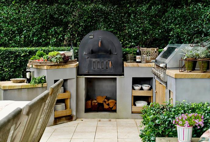 """This [outdoor kitchen](https://www.homestolove.com.au/entertainment-ready-outdoor-areas-2741 target=""""_blank"""") contains all the essentials within easy reach. The pizza oven and barbecue, along with storage cupboards make outdoor entertaining relaxing. *Photography by Scott Hawkins*"""
