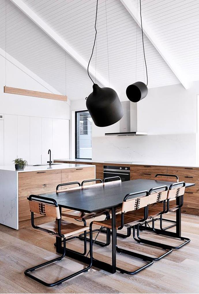 "These simple, yet classic [statement black pendants](https://www.homestolove.com.au/kitchen-design-inspiration-5869|target=""_blank"") create a less-is-more aesthetic in this kitchen area. *Photography by Terence Chin*"