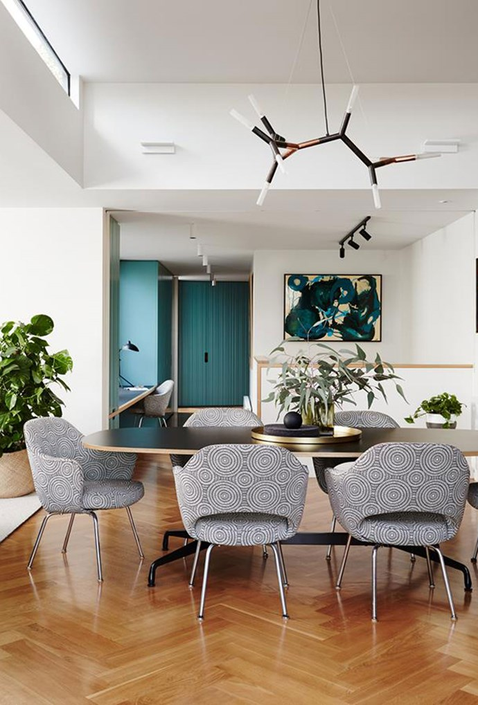 """The dining room of this [modernist](https://www.homestolove.com.au/renovated-modernist-melbourne-home-5581 target=""""_blank"""") Melbourne home, which includes an Eames segmented dining table and Eero Saarinen 'Executive' chairs, is framed by a light strobe chandelier. *Photography by Annette O'Brien*"""