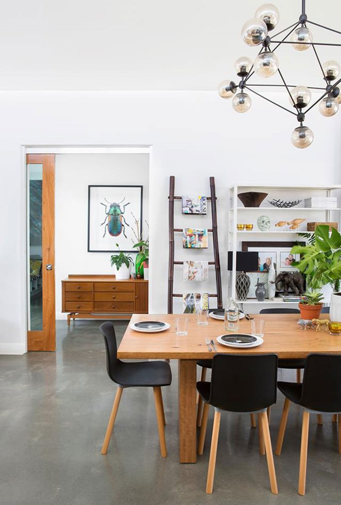 """Industrial statement lighting complements this sleek, monochrome dining space with punchy green highlights, found in a Perth home inspired by a [Bali villa](https://www.homestolove.com.au/a-suburban-perth-home-inspired-by-a-bali-villa-5181 target=""""_blank""""). *Photography by Angelita Bonetti*"""