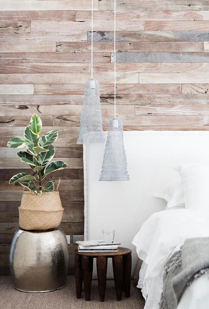 "A feature wall of weathered hardwood paneling in this [beachside home](https://www.homestolove.com.au/a-nature-inspired-home-in-beachside-perth-5137|target=""_blank"") in Perth is accompanied by textured bedside light pendants — a contrast to the predominately white colour scheme. *Photography by Bo Wong*"