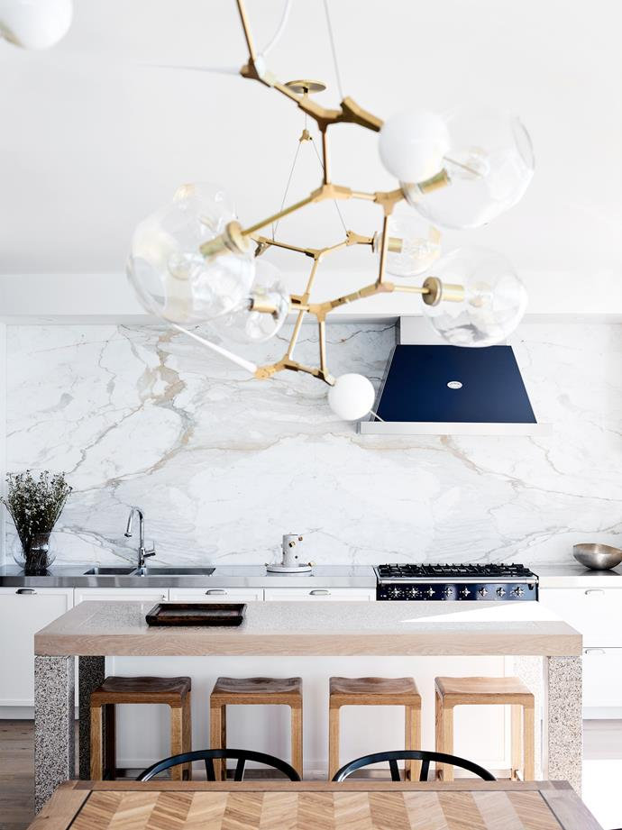 In the kitchen, honed Calacatta Oro Grigio marble splashback from Corsi & Nicolai. Lacanche rangehood and cooktop. Custom oak stools by David Hicks. Lindsey Adelman chandelier.