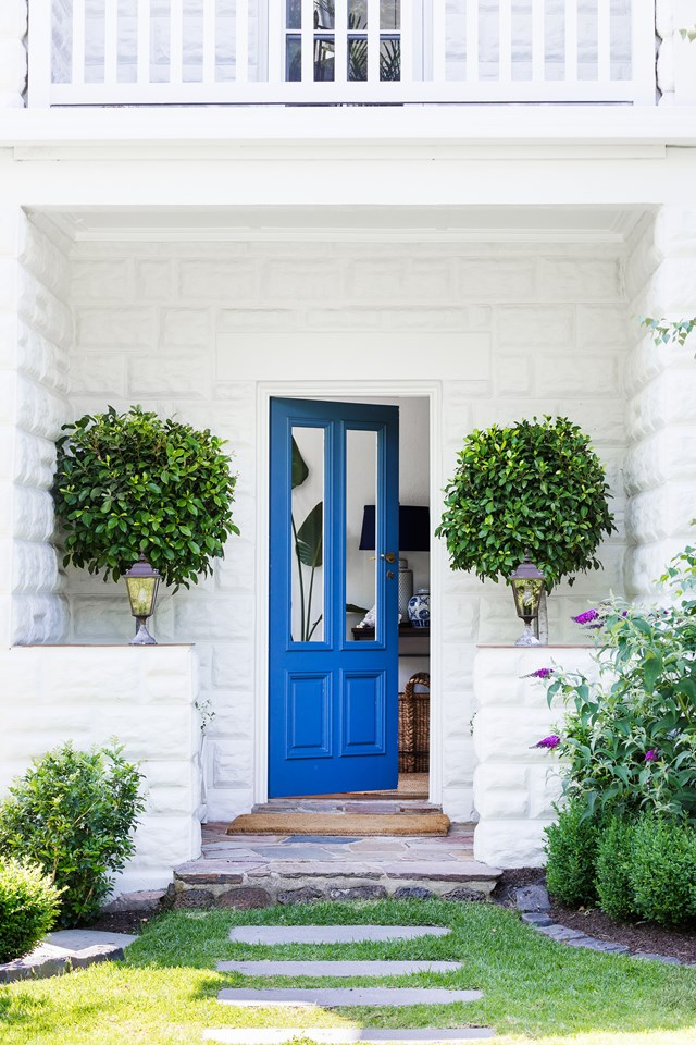"""A fresh white exterior and bold blue door (Taubmans Stained Glass) sum up the coastal-Hamptons scheme for this [Mornington Peninsula home](https://www.homestolove.com.au/hamptons-style-home-in-coastal-victoria-6266