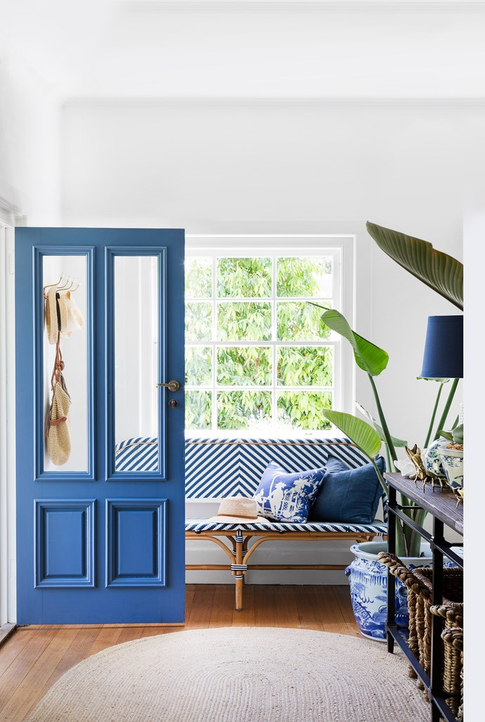Glazed door panels give visitors a glimpse of the home's breezy decor. Once inside, a woven bench from Lincoln Brooks gives an impression of deep ease.