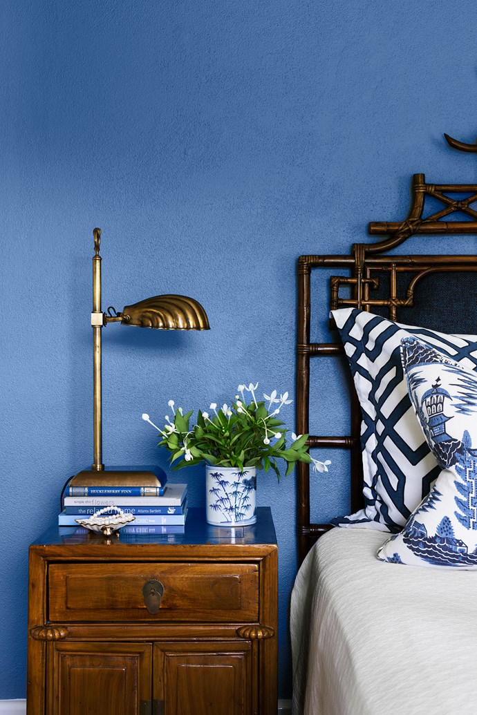 Brass, timber and dark-stained cane look resplendent against a wall in Dulux Blue Oar. Custom bedhead.