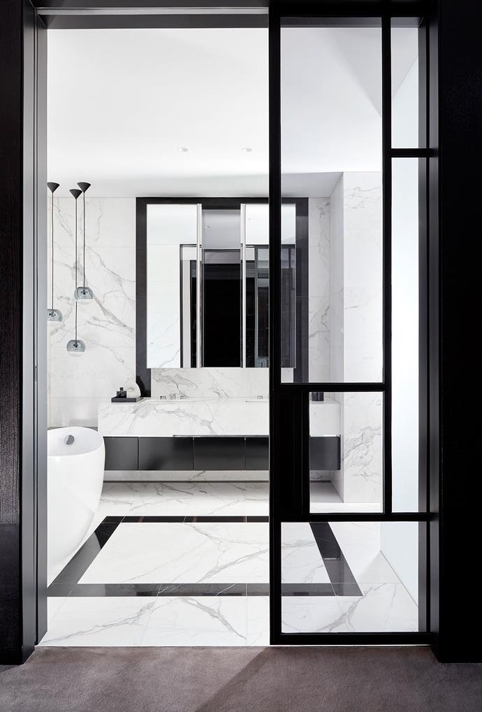 Black steel-framed glass doors into the master bathroom which is swathed in Calacatta and Nero Marquina marble.