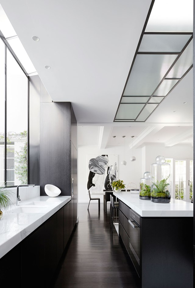 "Running along the length of the island bench is a skylight constructed from ribbed glass. The texture of the glass diffuses sunlight throughout [the monochromatic Melbourne home](https://www.homestolove.com.au/monochromatic-home-melbourne-toorak-6270|target=""_blank"") creating a soft, warm glow rather than a harsh glare. *Photo: Lucas Allen / Story: Belle*"