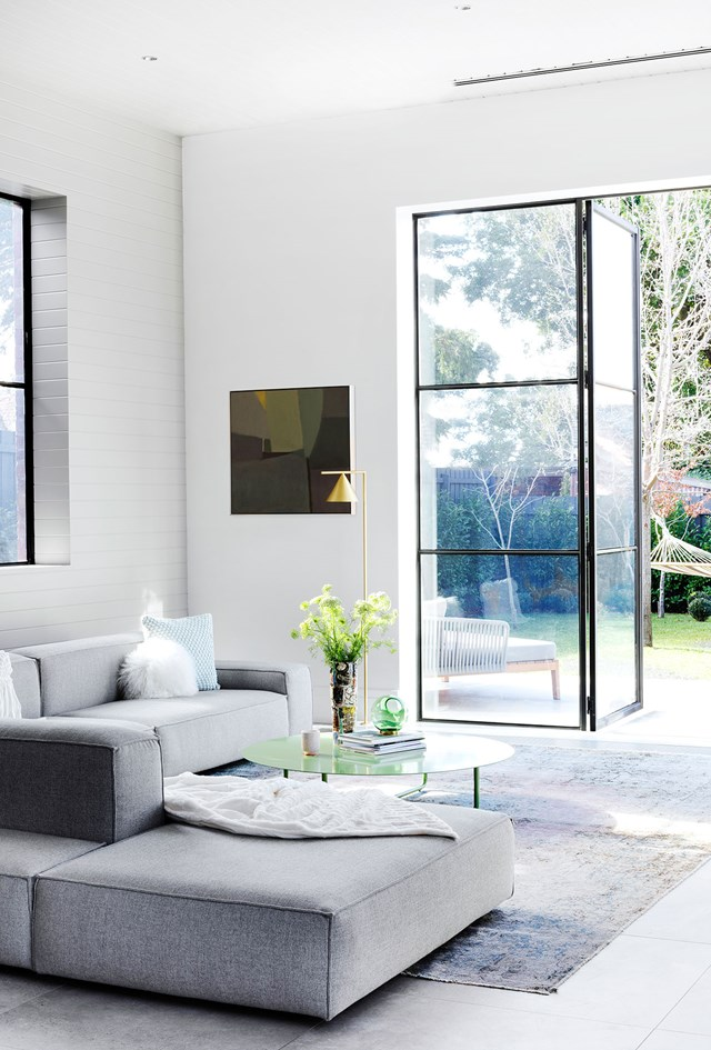 Black steel-framed windows and doors create a modern industrial feel.
