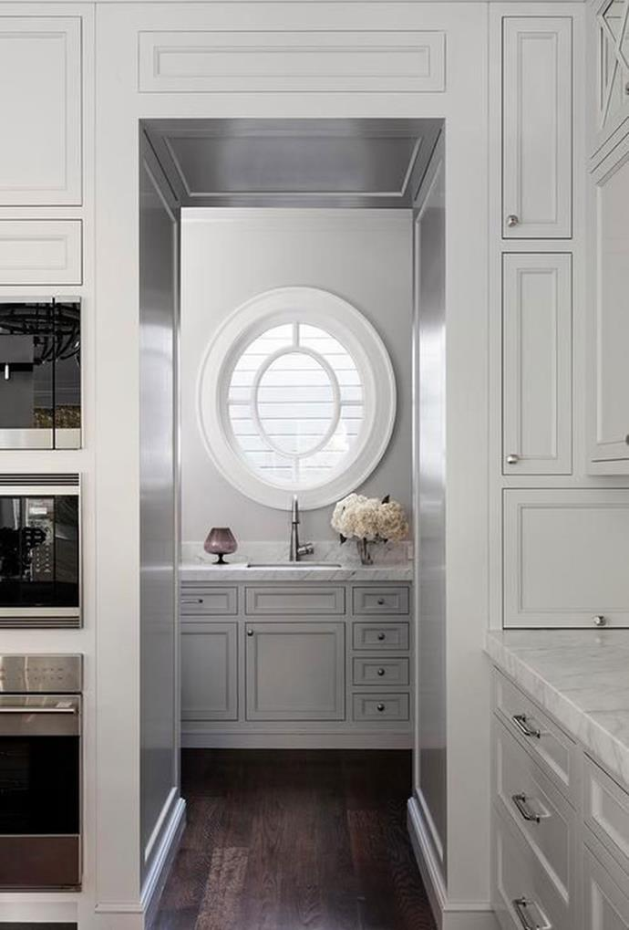 "A marble bench top and dark wooden flooring, along with a circular window creates a luxurious [butler's kitchen and pantry space shared by DecorPad](https://www.pinterest.com.au/pin/341288478002642323/|target=""_blank""