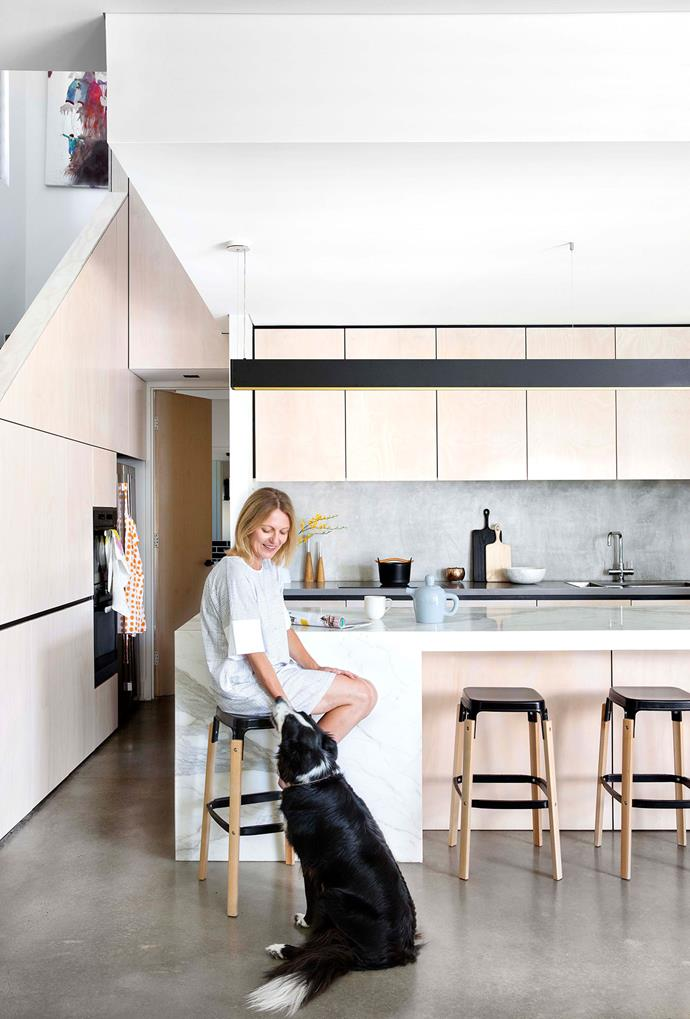 Sarah with Billie, the family's border collie/kelpie cross. Behind her, the concrete splashback and Calacatta marble island are in perfect harmony. Austral Multiply plywood cabinetry with limed polyurethane finish and black melamine detailing. Integrated Miele oven and microwave. For similar stools, try Anibou. Suspension light, Lighting Options Australia. Designer buy: Large 'Alfredo' vase (on side table, opposite top left), $435, Georg Jensen.