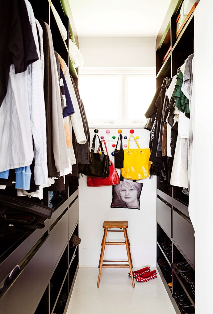 The dark cabinetry in this walk-in wardrobe is contrasted by a colourful bag rack hung on an empty wall space. *Photo: Chris Warnes | Story: Real Living*