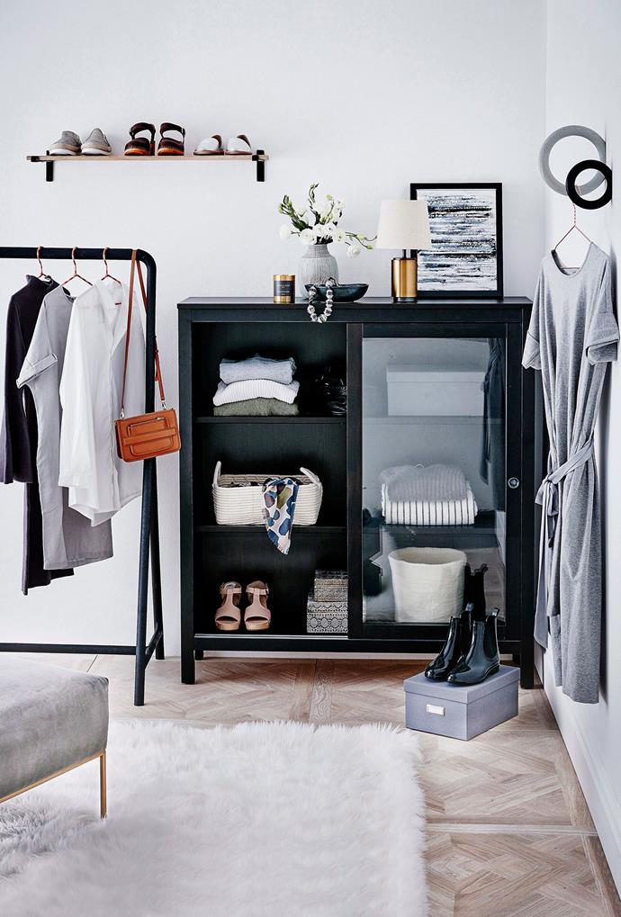 A glass-framed cabinet, black steel clothing rack and wall shelf are complemented by a faux fur rug and grey-hued ottoman in this walk-in wardrobe. *Photo: Will Horner | Story: Australian House & Garden*