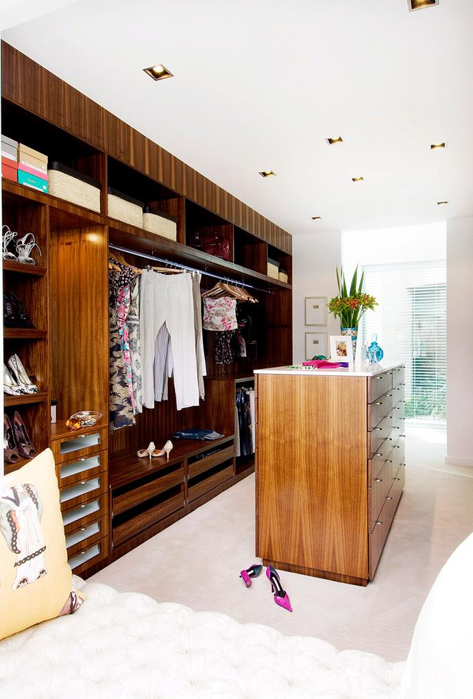 "Wooden cabinetry spanning the whole wall of this walk-in wardrobe allows for maximum [storage and neat organisation](https://www.homestolove.com.au/how-to-organise-your-wardrobe-6984|target=""_blank""). *Photo: Steve Ryan 