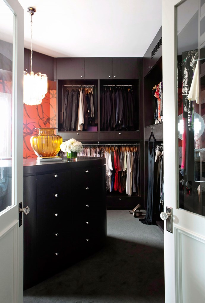 This deep-hued walk-in wardrobe features an island of drawers and a large shelving space, together with abstract art and a luxurious light pendant. *Photo: Maree Homer | Story: Australian House & Garden*