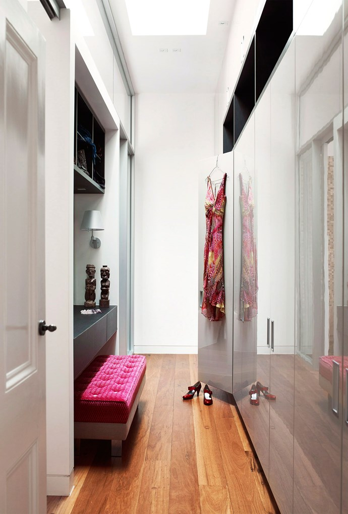 Glossy neutral cabinet doors are brought to life by a pink ottoman in this walk-in wardrobe. *Photo: Derek Swalwell | Story: Australian House & Garden*