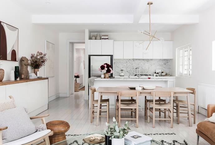"""The kitchen's Carrara marble splashback and benchtop were non-negotiables for Carla. """"The geological history is mapped in the stone and it has a lot of depth and beauty,"""" she says. Many of the other items in the room were sourced inexpensively – the cabinets came from her brother-in-law's house, the dining table from Ikea's bargain corner and the chairs were bought second-hand from an auction house."""