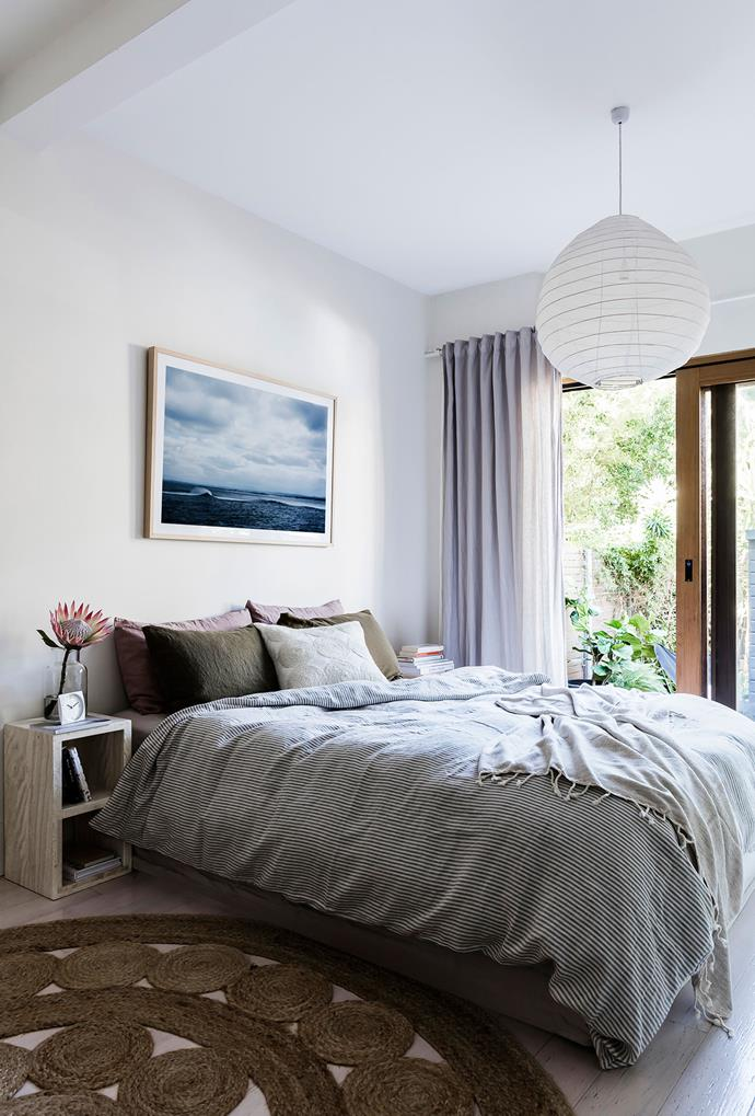 """Carla's bed is dressed with a quilt cover from InBed, linen throw from Adairs and wool-embroidered cushion cover from Città. The side table is by Sarah Ellison for Clickon Furniture and the alarm clock is also InBed. """"The beautiful Tasmanian seascape was taken by my friend Justine Kerrigan,"""" she adds."""